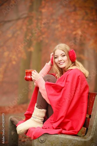 Girl in autumn park enjoying hot drink