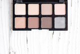 Top view of pink and brown tone make up palette on white wooden background - 176286723