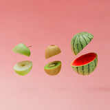 Fototapety Watermelon, apple and kiwi sliced on pastel pink background. Minimal fruit concept.