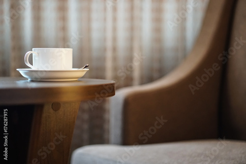 white coffee cup on the table by a sofa couch in hotel room