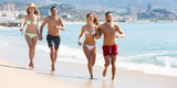 Adults running at sandy beach