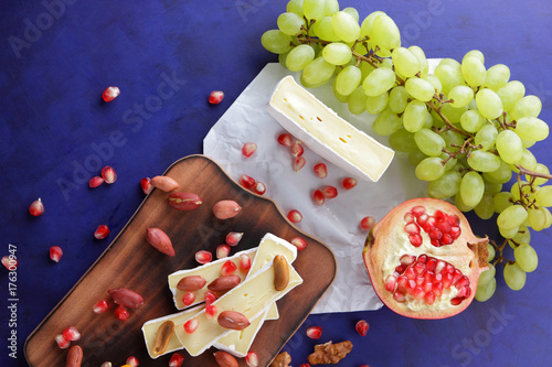 Camembert cheese, orange hard cheese, green grapes, peanuts, walnut and pomegranate seeds on a wooden board on a dark blue background