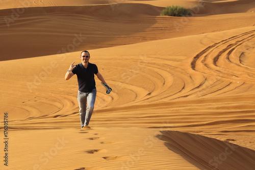 Staande foto Dubai Man walking alone in the sunny desert