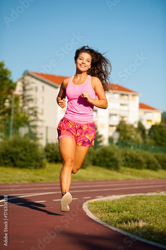 Poster Jogging active young woman runs on atheltic track on summer afternoon
