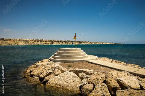 Fotobehang Cyprus A lifeguard flag at small pedestal viewpoint at Secret Paradise of Aluminos beach