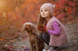 Little girl sitting with dog together on nature at the autumn day, art portrait