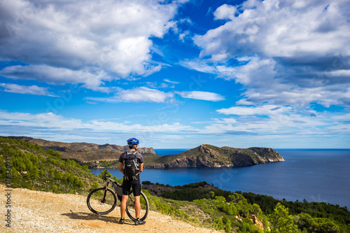 Fotobehang Purper a young guy on a mountain bike trails in Spain and takes a photo on a white phone in the background of the Mediterranean sea of the rocky coast of the Costa Brava. k.