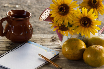 wuite note paper, oranges, wood pencil and mexican handmade, wild sunflower inside a watering cup on moody wood