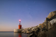 Seascape of a small lighthouse with their reflections on the sea at sunset. A man is fishing under the starry sky. Photo taken at sunset in Sabaudia beach, Italy