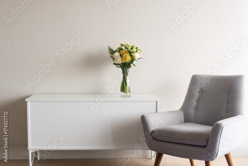Szary fotel retro obok biały kredens z szklanej wazonie kremowych i żółtych kwiatów na neutralnym tle ściany