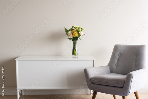 Poster Grey retro armchair next to white sideboard with glass vase of cream and yellow