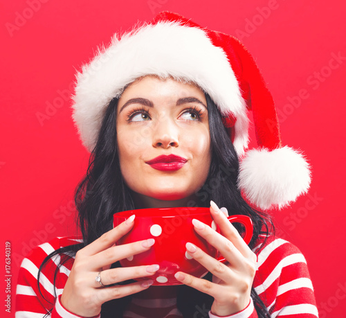 Wall mural Happy young woman with Santa hat drinking coffee