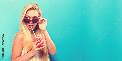 Deurstickers Sap Happy young woman drinking smoothie on a solid background