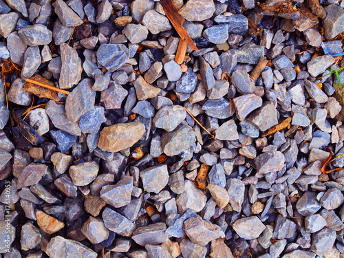 Tuinposter Stenen Vary size blue grey granite construction wet rock and stone texture floor, with small brown fallen leaf background