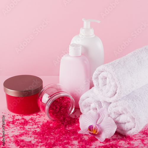 Fotobehang Spa Towels with shower gel, scrub, sea salt and body lotion on pink background.