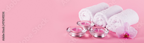 Towels, candles and orchid flowers for a spa relaxation on a pink background.