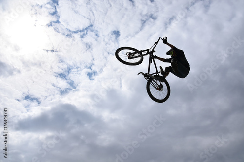 Deurstickers Silhouette of a young man freestyle stunt cyclist flying in the sky