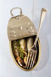 smoked oily sprats in a can with thyme and a fork - 176345575