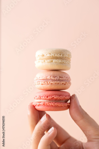 Spoed canvasdoek 2cm dik Macarons Woman hand holding three macarons on a pastel background. French confectionery. Sweet food