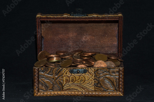 Old coffer with coins on a black background Poster