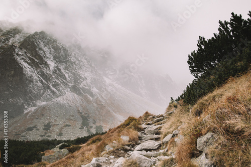 Mountain track heading to foggy mountain
