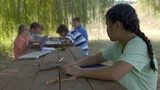 Lonely girl sits alone looking sad at wooden table during an outdoor class at summer camp with other students in background. 4K - 176362116