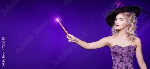 A beautiful woman, blond in a good witch costume on a purple background, holds a magic wand and conjures, focus. Young girl. Halloween - 176363313
