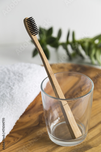 Bamboo toothbrush in a glass with white towel
