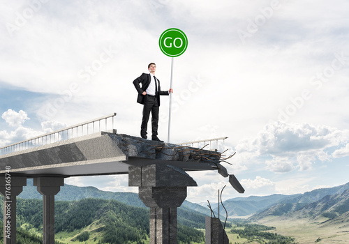 Fototapeta Young businessman holding street safety sign.