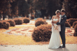 Newlyweds groom and bride walking in autumn park - 176367926