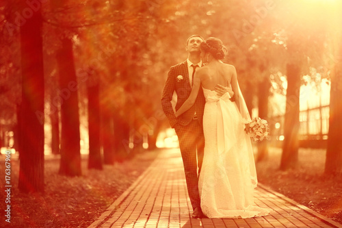 Newlyweds groom and bride walking in autumn park - 176367960