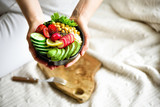 Girl in white jeans holds in hands fork, vegan breakfast meal in bowl with avocado, quinoa, cucumber, radish, salad, lemon, cherry tomatoes, chickpea, chia seeds. Top view, copy space. Clean eating. - 176369702