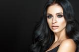 Piękny kobieta portret na czarnym tle. Seksowny makijaż i długie kręcone włosy.