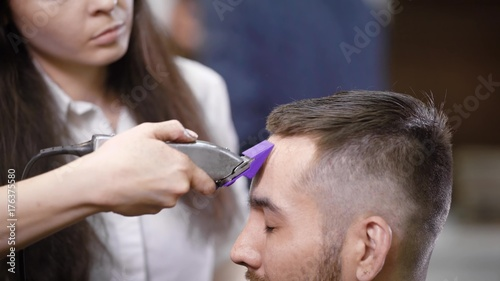 Close up of professional female hairstylist dressed in casual clothes is serving client in barbershop using modern trimmer. Young man is getting trendy haircut sitting on chair closing his eyes.