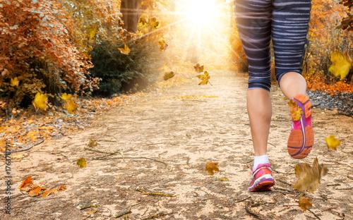 Tuinposter Jogging Beine einer weiblichen Joggerin im herbstlichen Park mit herabfallendem Laub