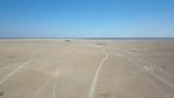 Animal tracks disappearing into the flat horizon of the Kalahari aerial drone shot - 176380128