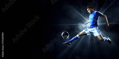 Fotobehang Voetbal Soccer player performs an action play on a dark background. Player wears unbranded sport uniform.