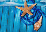 Beautiful summer sea background. Blue wooden boards, blue decorative rope, seashells. - 176384188
