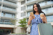 Low angle view of good-looking Asian woman with shopping bags and coffee texting on smartphone