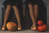 Happy halloween! Female feet in stockings with an orange pumpkin - 176387115