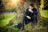 Handsome young man leaning against tree in autumn, wearing black coat - 176388512