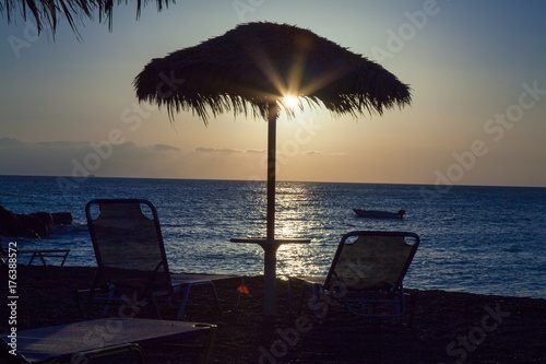 Spoed canvasdoek 2cm dik Zee zonsondergang Beach umbrella and sun beds on the sea beach at sunset