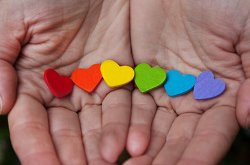 hearts of the color of the rainbow in hands. Background of LGBT