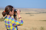 Woman tourist on safari in Africa, watching african savannah wildlife with binoculars  - 176391948
