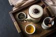 Tea set on wooden tray on black stone background