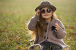 Little girl with sunglasses and hat sitting on a grass in autumn clothes