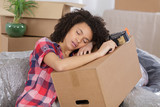 woman sleeping over package for house moving - 176409557