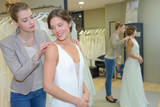 female trying wedding dress in shop with assistant