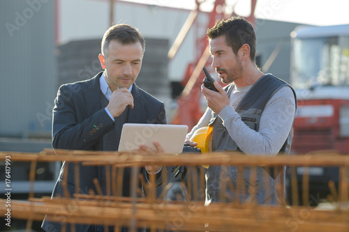 middle-aged male worker using walkie-talkie with colleague - 176417993