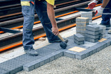 Worker hand with hammer places concrete pavement stone 2 - 176422989